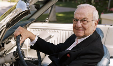 Lee Iacocca sitting in an original Ford Mustang.