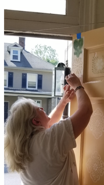 Sarah, hard at work to transform a neighborhood door.
